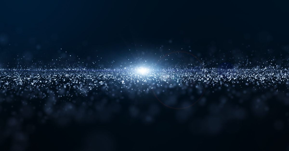 A dark, space-like background with a light in the center and particles of light spreading out from it like stars.