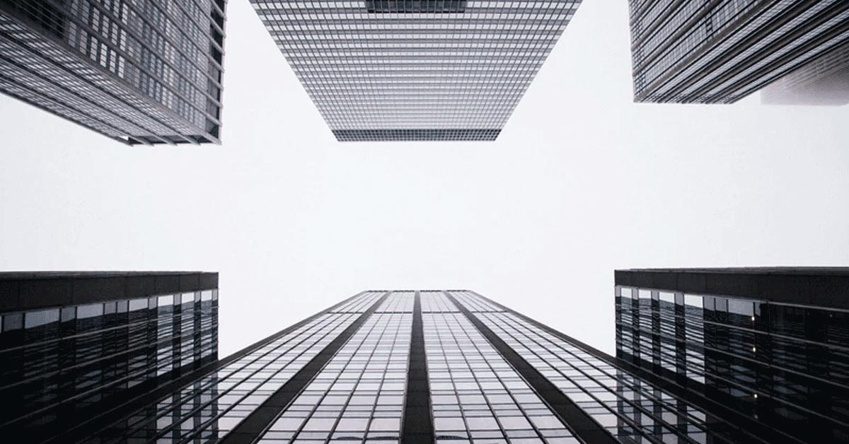 Looking up at dark, glassy buildings with white sky overhead.